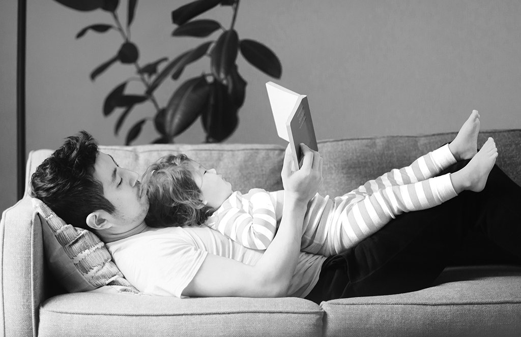 Dad and daughter reading on the couch